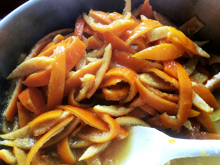 candied orange peels simmering in syrup