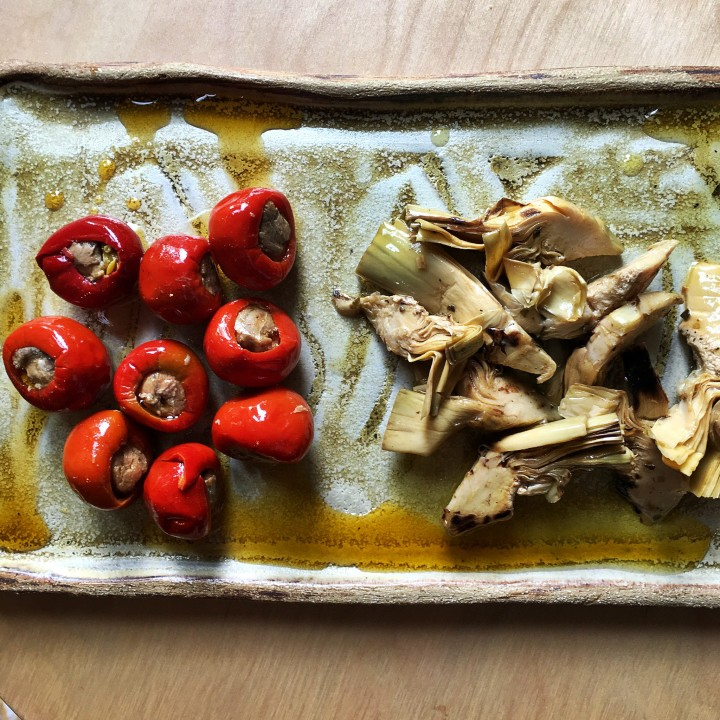 stuffed peppers and preserved artichokes on an handmade ceramic dish